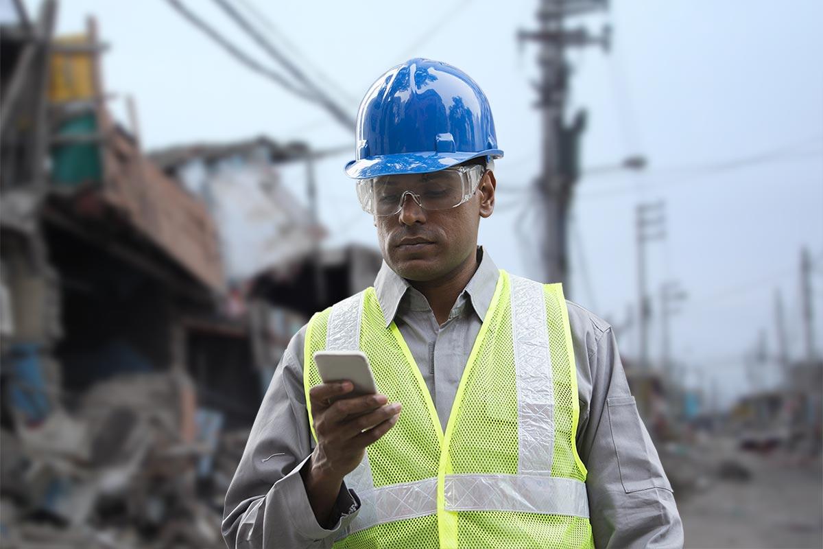 man looking at phone app in natural disaster zone